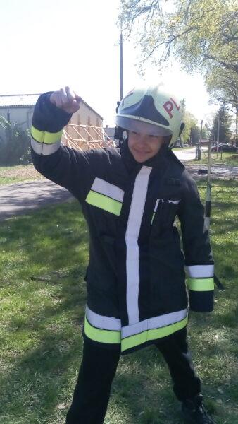 A képen Kiss Milán 6. a osztályos tanuló látható a tűzoltás előtt védőruhában.
